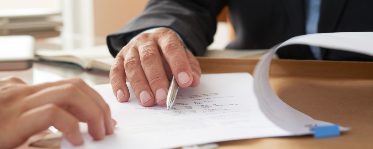 Close-up of businessman examining business contract and signing it at the office desk